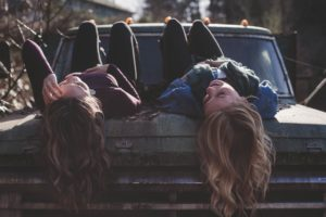 two women laying on old car laughing
