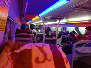 view of interior of the bus with blankets on seats