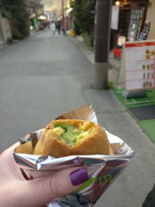 a hand holding a foil wrapped cream puff filled with green cream, a delicious part of life after keto