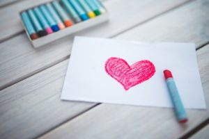 red heart drawn on white paper with pastels in box