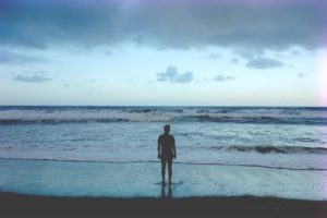 man standing with feet on the shore looking out at ocean