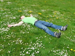 man laying flat in grass with flowers