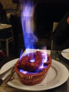 a dish with sausage and flames in a restaurant
