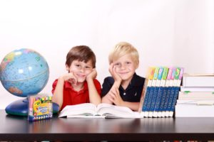 two boys with books and markers and a globe