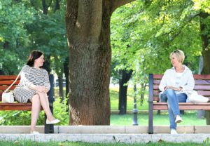 two women on different park benches talking