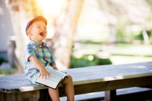 a child on a bench with a book laughing
