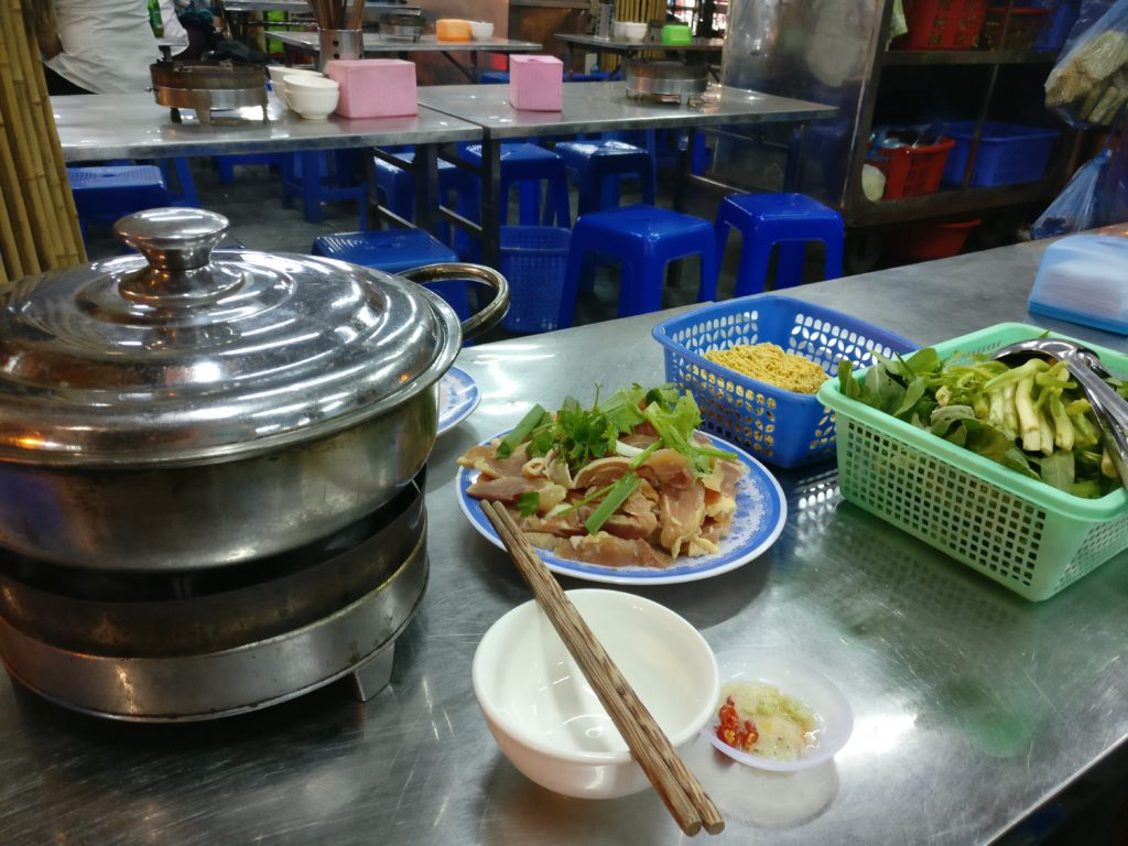 a hot pot with a bowl of raw meat and basket of vegetables ready to be cooked at the dong xuan night market