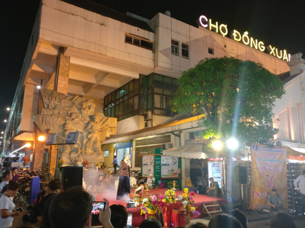 A woman is on stage at the Dong Xuan Night Market singing. She is wearing plain black pants and a brown top. The view is not great as there are many distractions around.