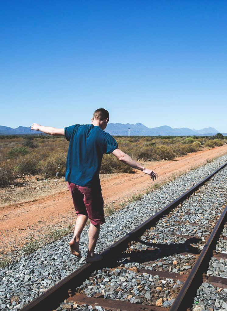man balancing on a train track to represent the life balance you can reach through narcolepsy coaching