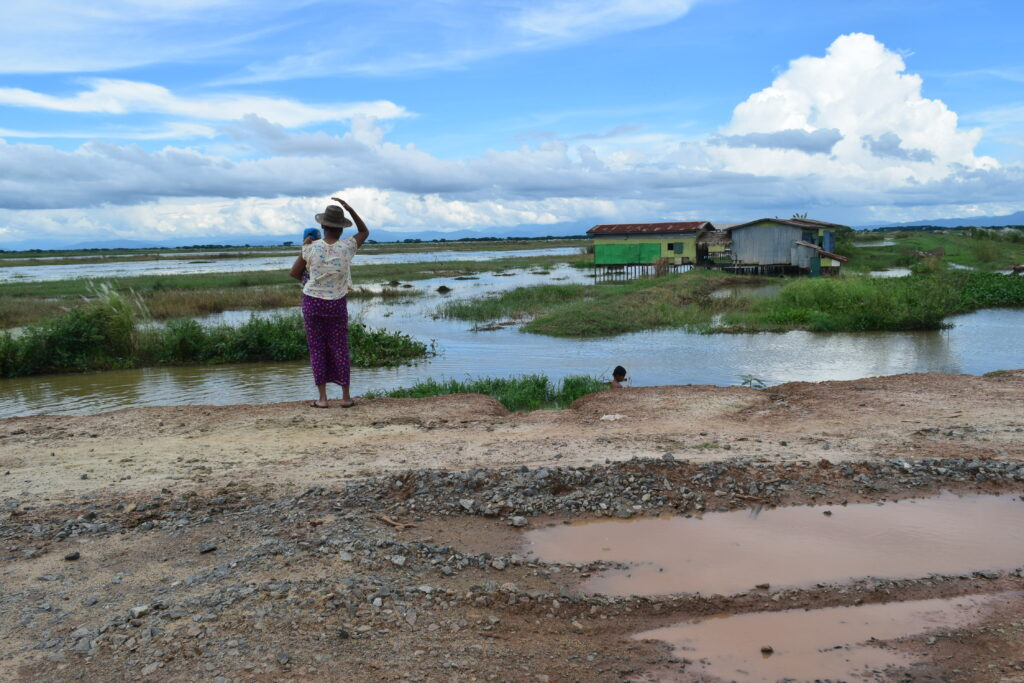 a view of a rough road in Myanmar with a woman holding a baby looking out over rice paddy