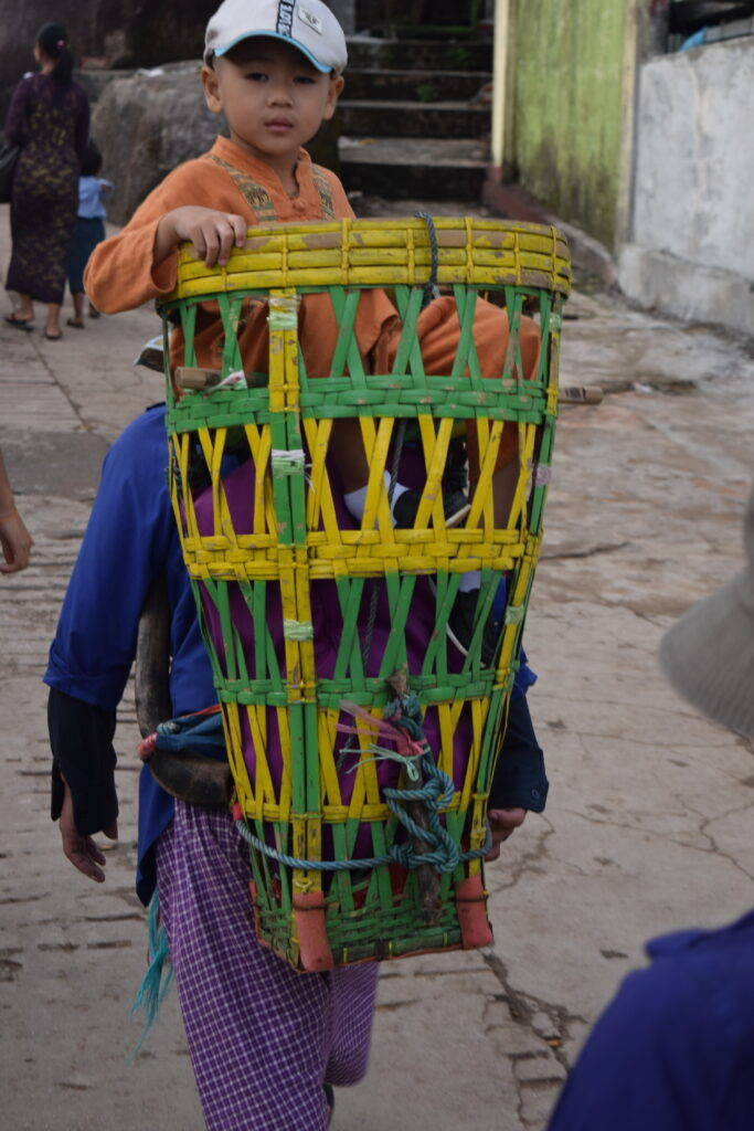 A child sits in a basket backpack going up to golden rock