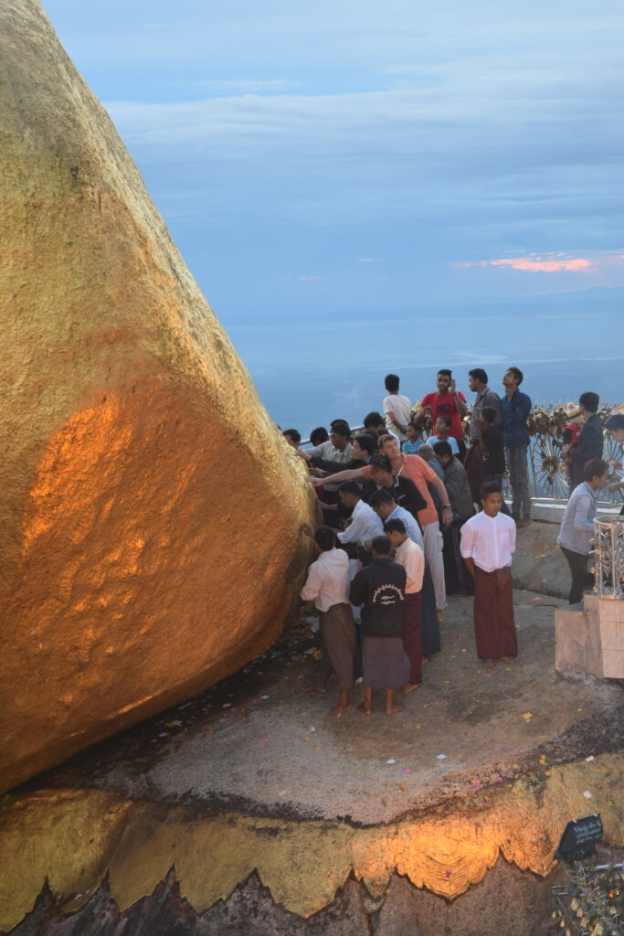 men touching Golden Rock on Thadingyut