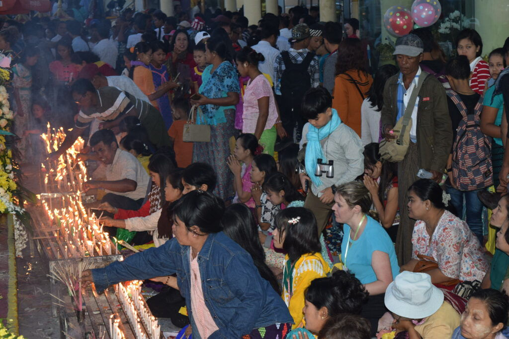 people praying and lighting candles at Golden Rock on Thadingyut 2018