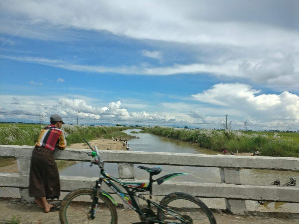 Man looking over a bridge next to his bike in Myanmar