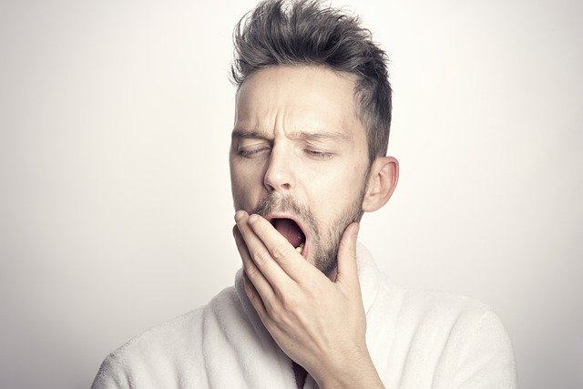 man being vulnerable with narcolepsy revealing he is tired by yawning openly