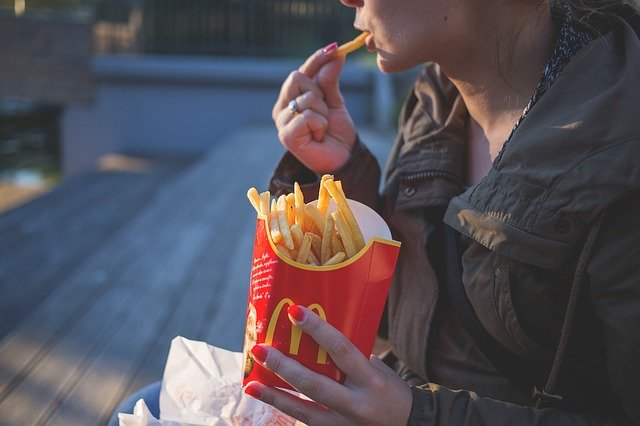 Woman feeling guilty eating french fries